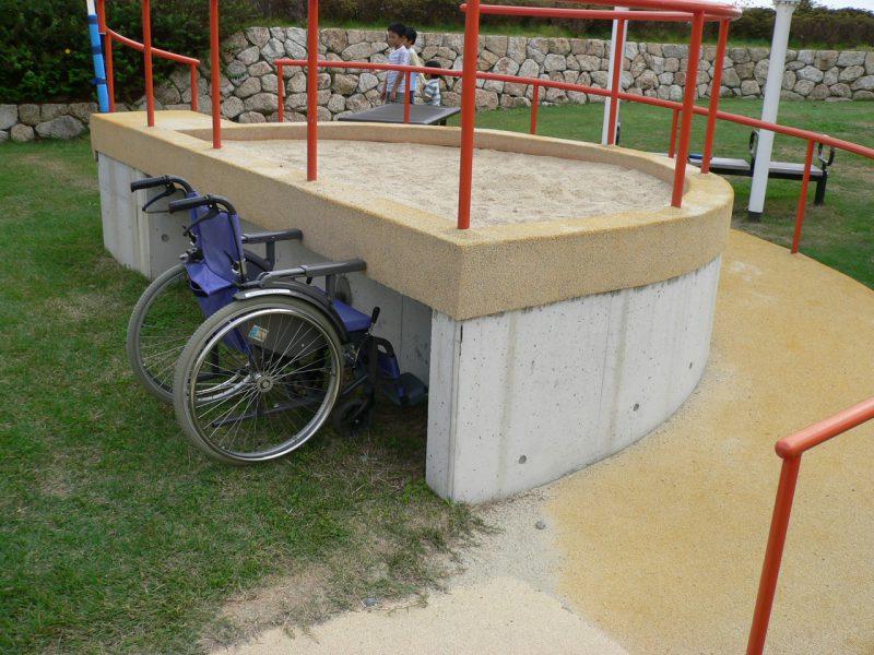 写真:テーブルの高さに作られた半円形の砂場。直線の部分の壁には蹴込みスペースがあり、車いすがアクセスしやすい。下は芝生