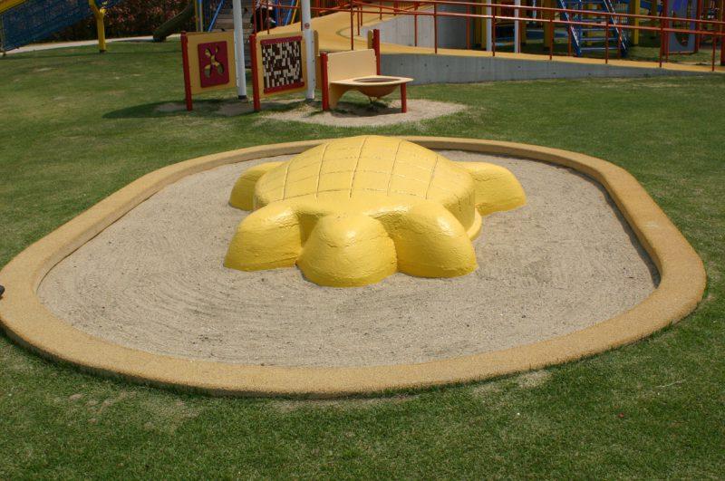 写真:芝生の中にある楕円形の砂場。砂場の中央には黄色のカメ