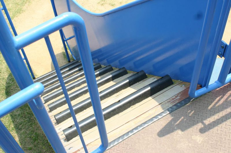 写真:急傾斜のクライミング遊具への開口部。車いすが通らない幅の柵がある