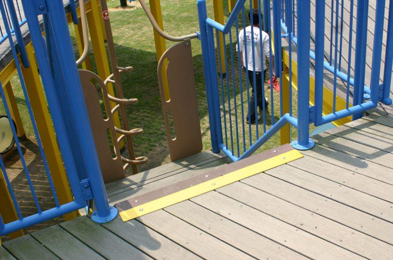 写真:階段を数段下りた先に遊具がある開口部。デッキも階段も同色で同素材だが、注意喚起のため開口部の床の縁に黄色のラインが敷かれている