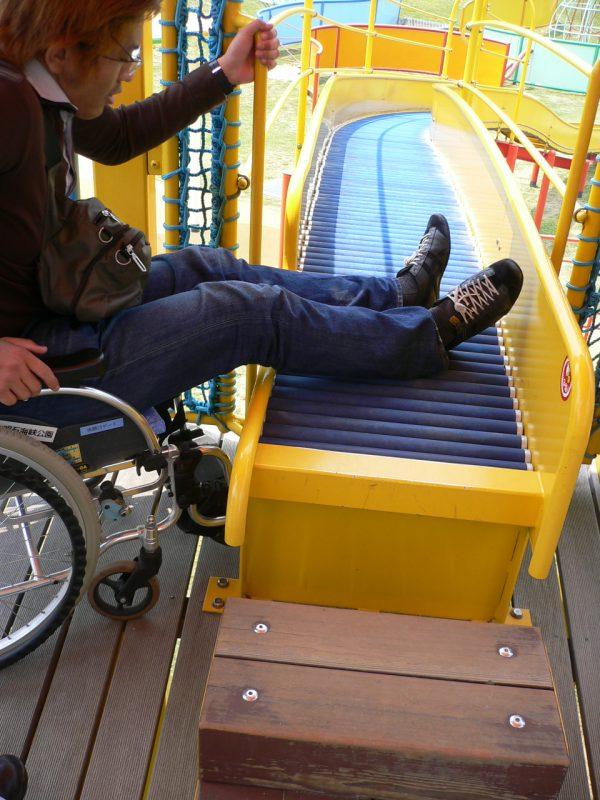 写真:スタート地点が床から50センチほどの高さに上げられた滑り台。車いすからアクセスする学生さん