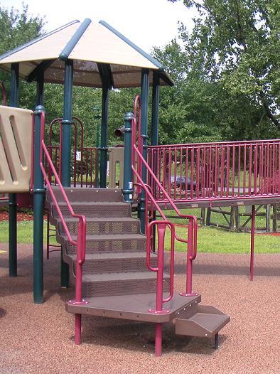 写真:複合遊具の2階デッキに行くための金属製の階段。車いすから乗り移るための段はやや広いデッキになっている