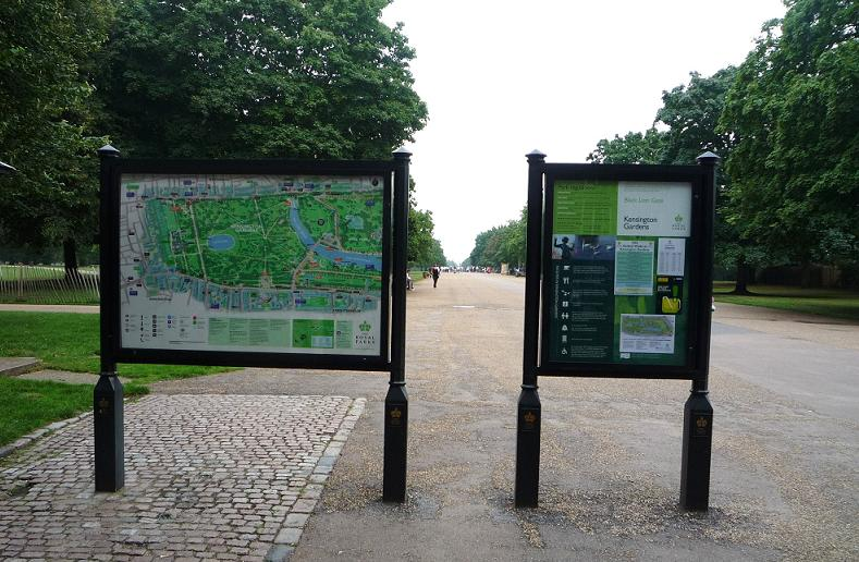 写真:並木の間をまっすぐに延びる広い園路。手前に公園の案内板