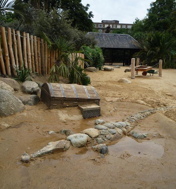 写真:地面に半分埋もれた状態の、等身大のワニの姿や木の宝箱
