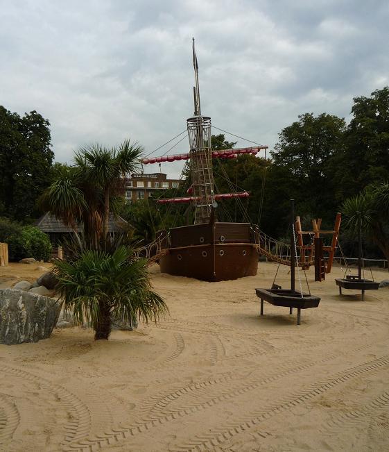 写真:広い砂場。大きな岩やヤシの木、小舟や帆船が配置されている