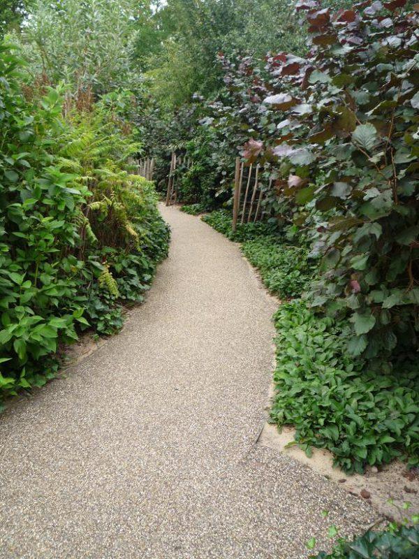 写真:緑の植栽の間をカーブして延びる園路