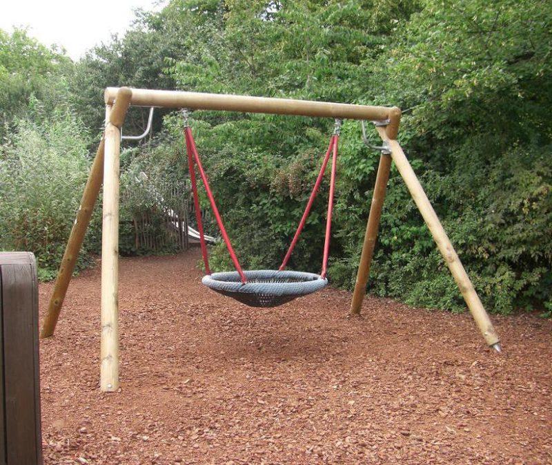 写真:大きな浅いざるを吊るしたような形のブランコ。背後の木々の奥に先ほどの滑り台