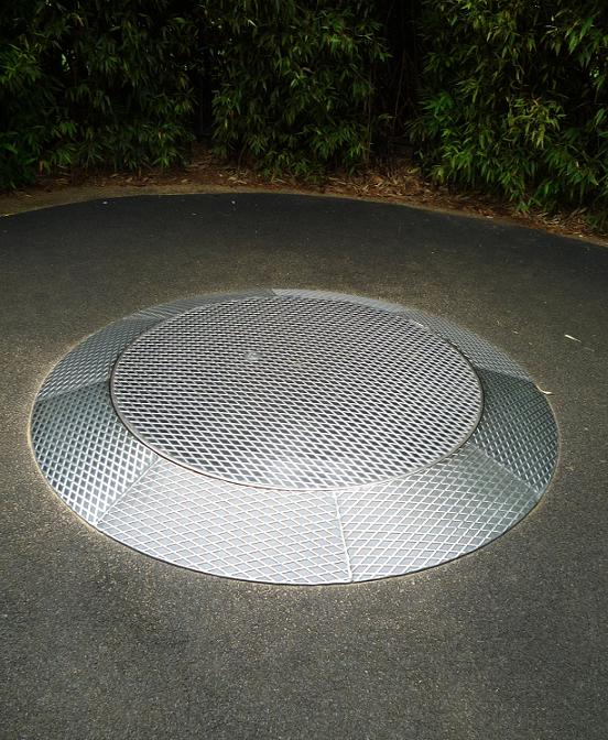 写真:地面から少し盛り上がったような形の金属製の円盤。中央の円く平らな部分が回転する