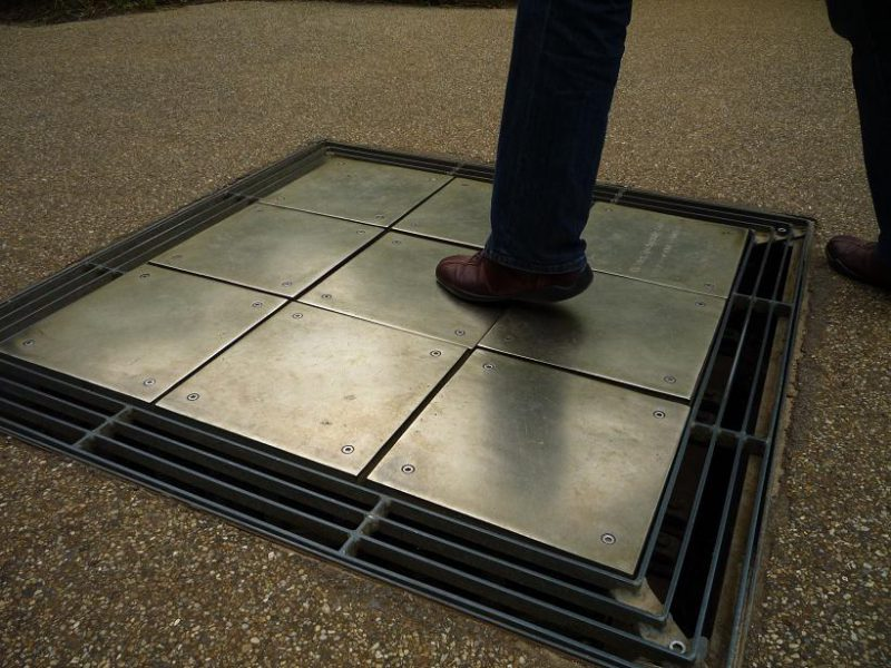 写真:地面に縦横3枚ずつ並んだ金属製の四角いパネル。中央のパネルを足で踏んでいるところ
