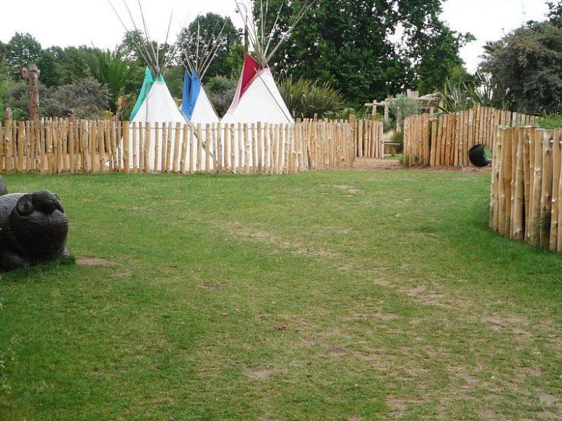 写真:芝生の広場の奥に、木の柵で周囲を囲んだアメリカインディアンの村