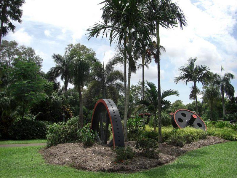 写真:高いヤシの木の根元に大きな歯車のモニュメントが置かれた庭園