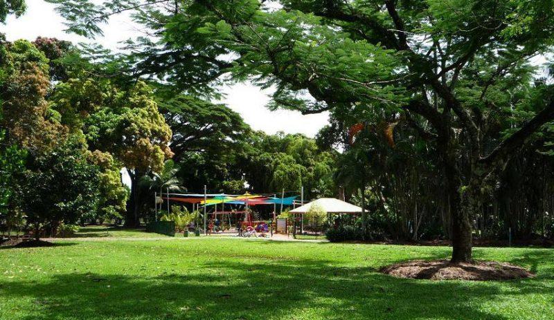 写真:緑いっぱいの公園の奥にあるカラフルな日除けや遊具