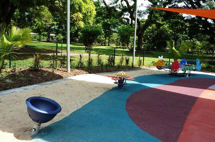 写真:遊び場。2種類の地面(カラフルなゴムチップ舗装と砂)がフラットに境界を接する。その境界に沿うように置かれたいくつかの遊具
