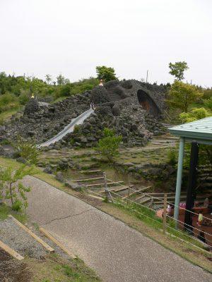 写真:溶岩谷の遊び場。黒い岩を積み上げた山の上につくられた滑り台