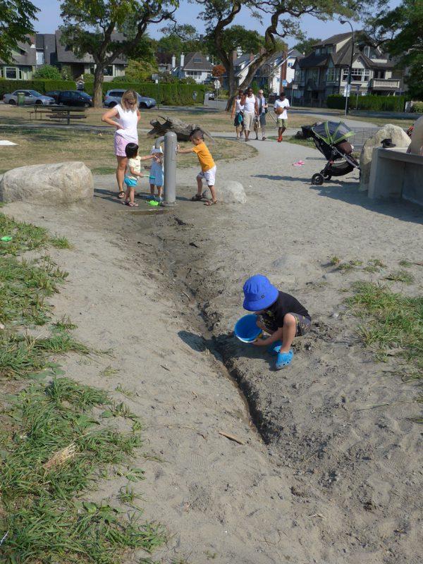写真:水の落ちる先は土の地面。子どもが掘ったまっすぐな溝に沿って流れるが、とちゅうで土にしみ込んでしまう
