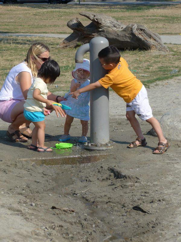 写真:お母さんに連れられたよちよち歩きの女の子たち。男の子がボタンを強く押し、水を出している