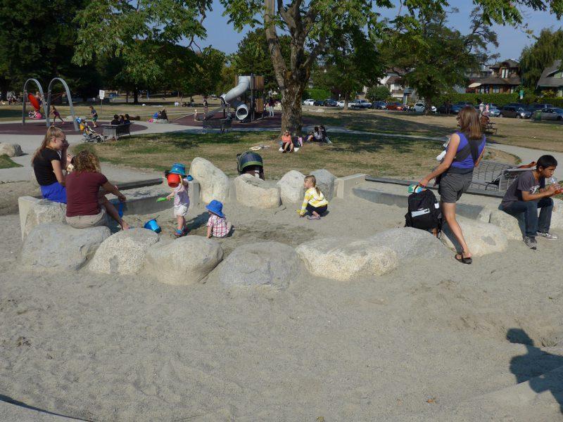 写真:砂場は、丸みのある大きな岩を並べて囲んである。中で遊ぶ数組の親子