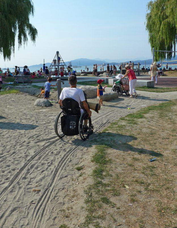 写真:砂の積もった園路を進む車いすユーザーたち