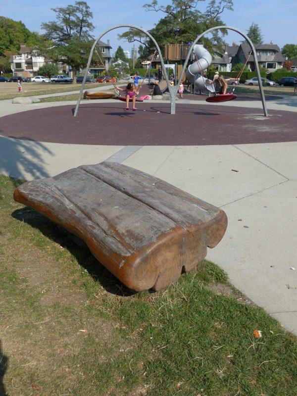 写真:木製ベンチ。大きな幹を縦半分に割り、木の風合いを残したまま滑らかに磨き上げたもの