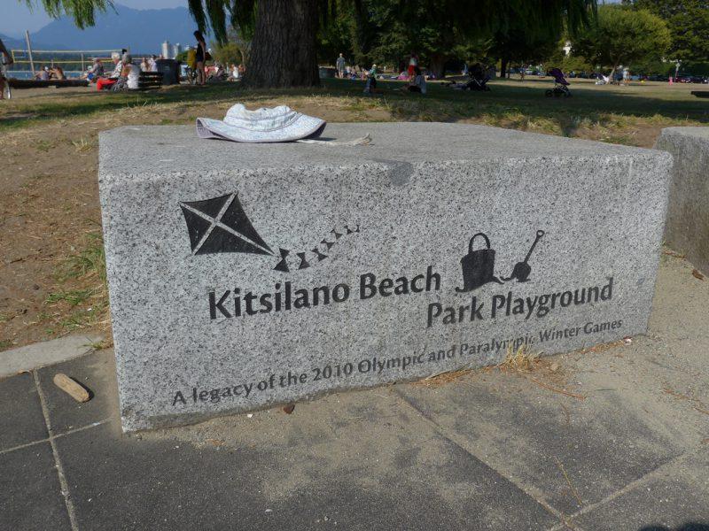 写真:岩を直方体に切り出したベンチ。側面には公園の名前と、凧揚げや砂遊びのイラストが刻まれている