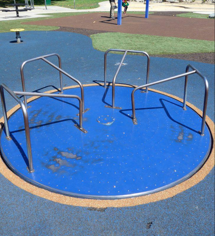 写真:直径2メートルの円い回転遊具。回転盤には一部分を除いてT字型の手すりが4本付いている