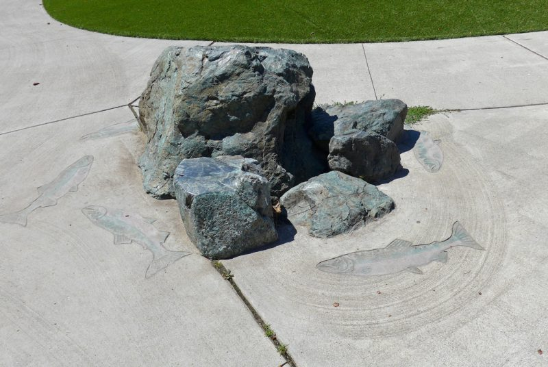 写真:園路脇に置かれた岩。地面には周囲を回るように泳ぐ4~5匹の鮭の姿