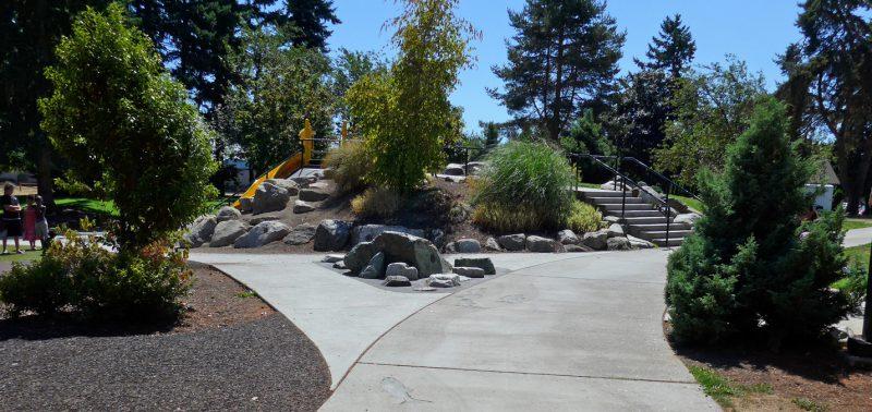 写真:園路の左に高さ2メートルほどの築山。正面以外の斜面は土や岩、草地に木々などの植栽