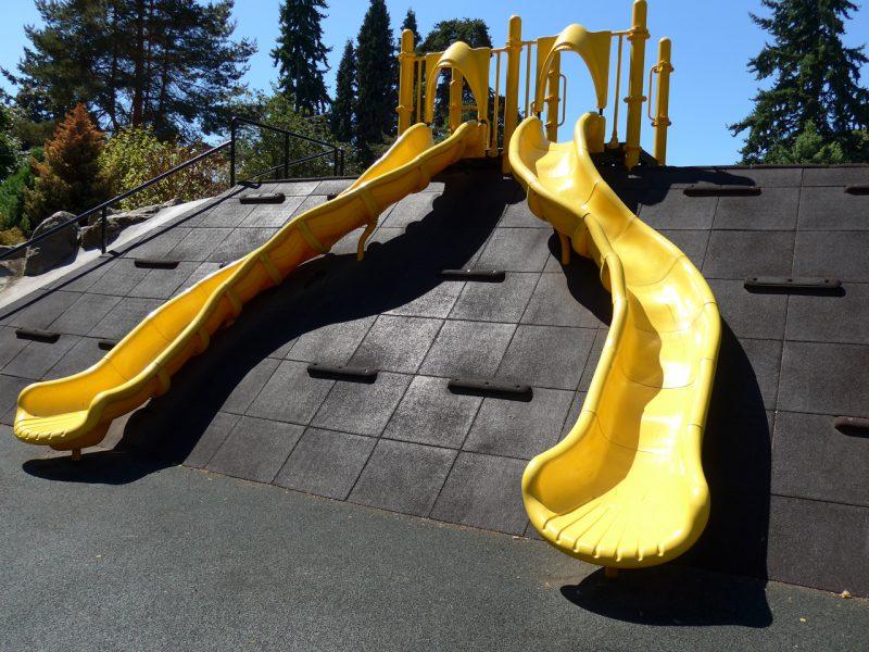 写真:2本の滑り台を備えた築山の正面。山肌は斜めに整地されゴムチップのタイルが貼られている