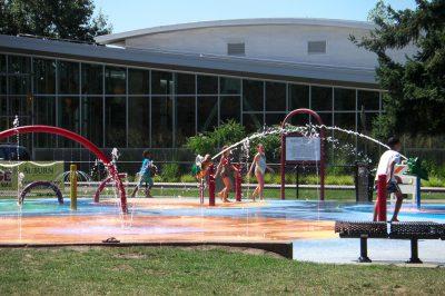写真:吹き出す水の間を、Tシャツと短パンや水着で駆けまわる子ども達