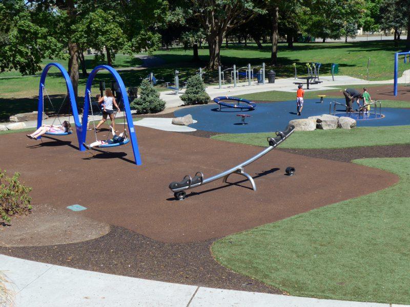 写真:遊び場の眺め。皿型ブランコや回転遊具で遊ぶ子どもたちの姿