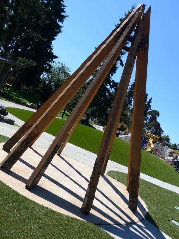 写真:長い9本の木の柱が円錐形に組まれたオブジェ