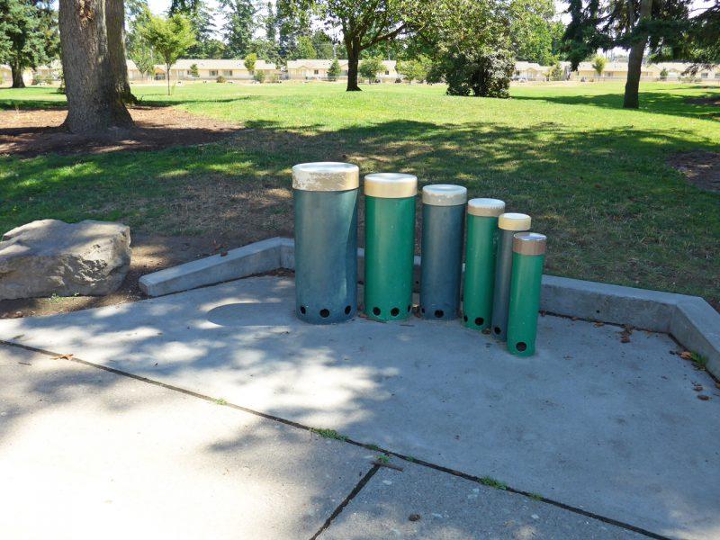 写真:高さと太さが違う円柱状のドラムが並んだコーナー。背後は一段高い草地になっている