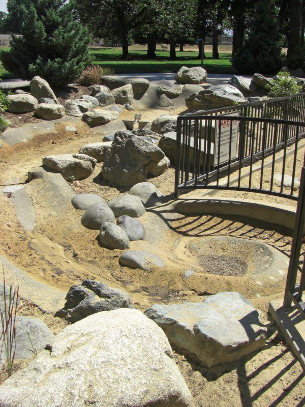 写真:柵の向こう側は緩やかにカーブした小川を模した水遊びコーナー。水は干上がっている