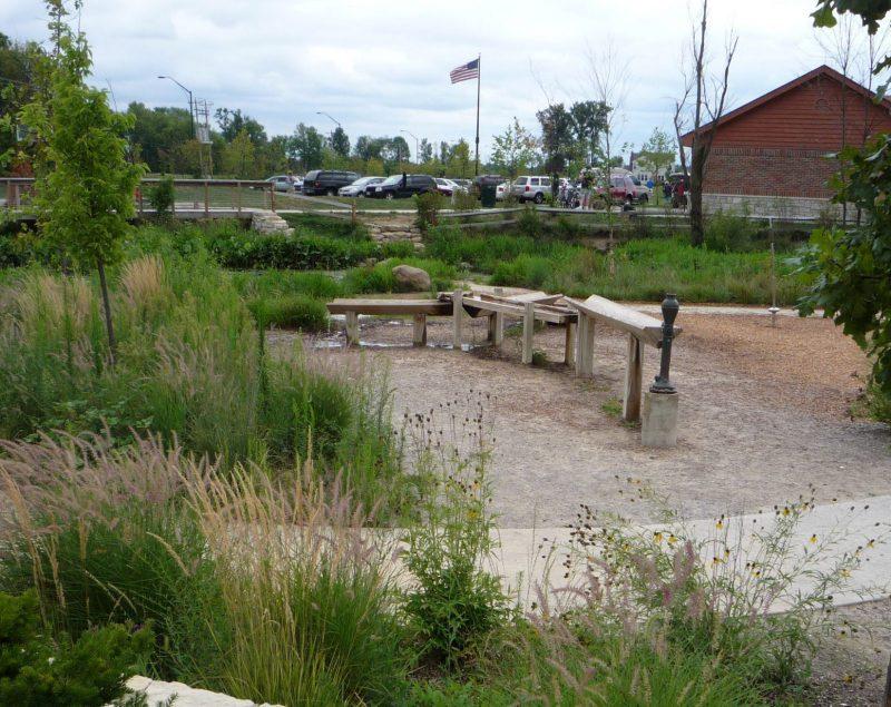 写真:歩道のそばのスペースに設置された木製の筧