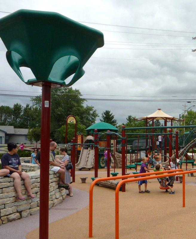 写真:遊び場を囲む石垣の上に腰掛けて子どもを見守る大人たち