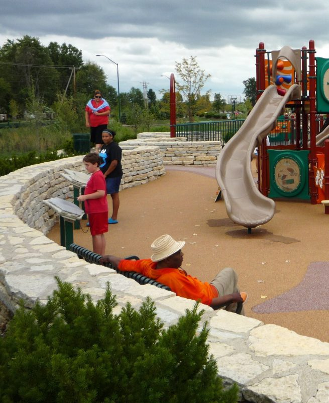 写真:石垣のそばで熱心に鉄琴を演奏する子どもたち