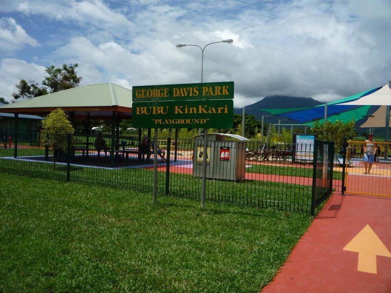 写真:フェンスで囲まれた公園の入り口。青々とした芝生に、公園名を記した看板が立っている