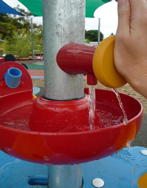 写真:水遊びテーブルの蛇口ボタン。押している間、水が流れ出る