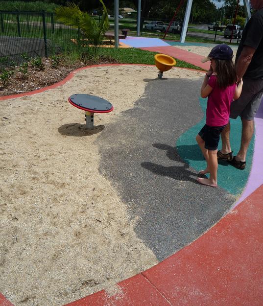 写真:砂場とゴムチップ舗装の境に設置されている、2機の回転遊具。どちらも1人乗り用