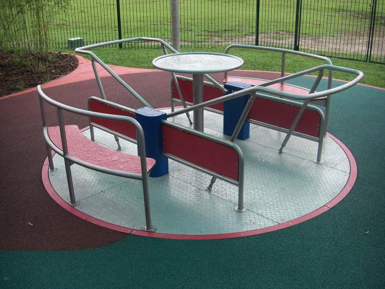 写真:直径2.5メートルほどの回転遊具。回転盤は地面と同じ高さで、3時と9時の位置から、車いすがテーブルを挟んで向かい合わせで乗り込めるほどの空間があるが、それぞれバーに囲まれている。12時と6時の位置にはベンチ