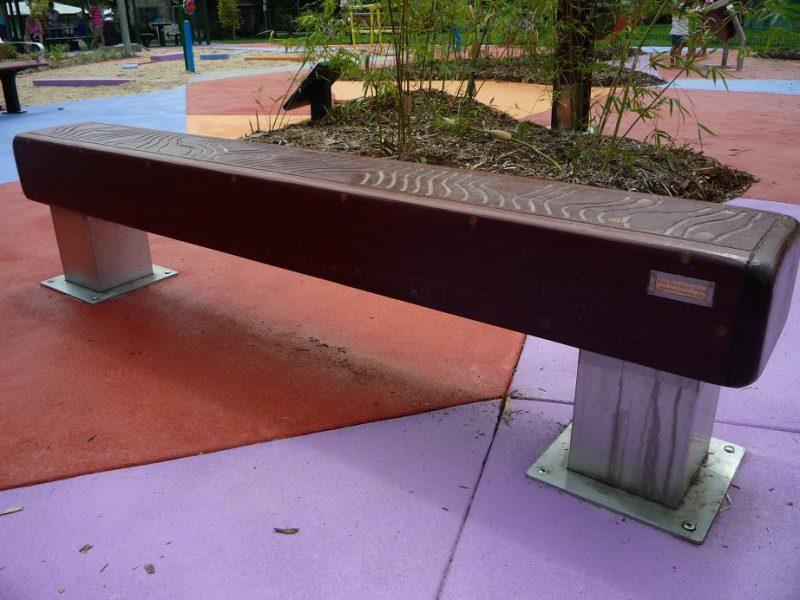"""写真:四角柱の木を横たえた、大きな平均台のような形のベンチ。座面には蛇行した美しい線が彫り込まれている""""Sonic Bench"""""""