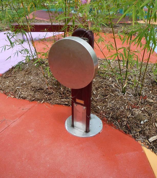 """写真:木の支柱の側面に、大きなステンレスの円盤が取り付けられている""""Rain Wheel"""""""
