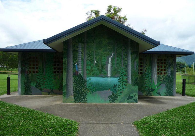 写真:トイレの外壁。うっそうと茂る森に抱かれた滝と湖や、木の陰に身を隠すヒクイドリの姿が描かれている