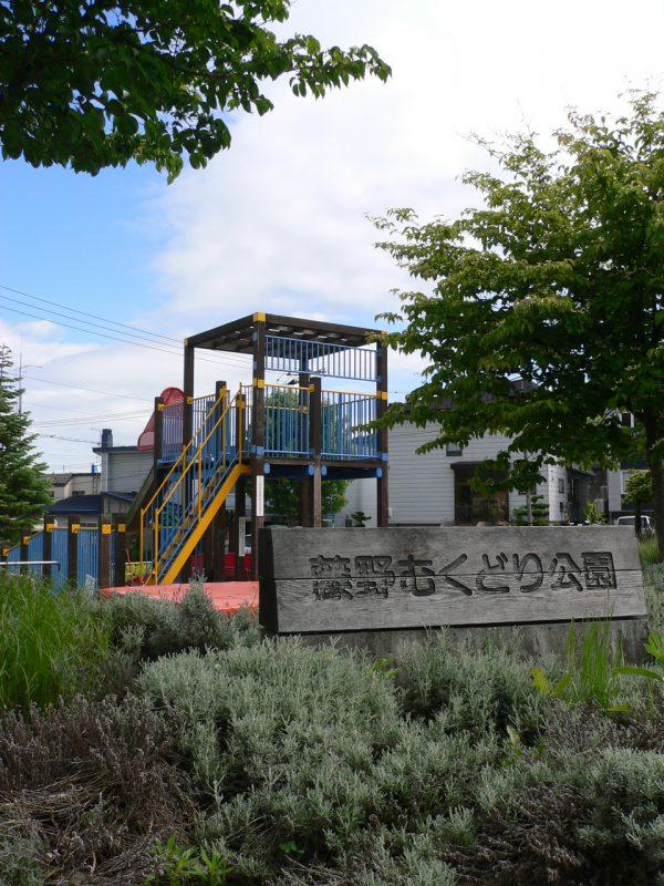 写真:公園の入り口。「藤野むくどり公園」と書かれた木の看板の背後に複合遊具
