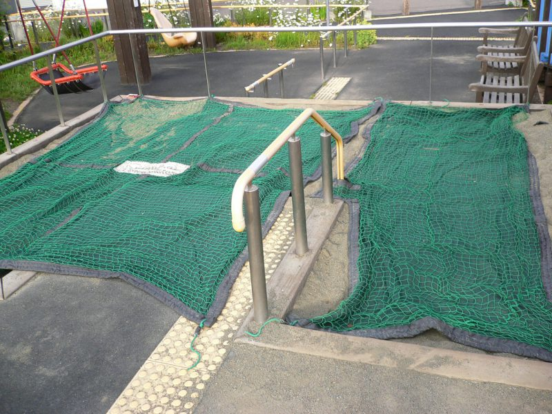 写真:砂場。園路からほぼフラットでアクセスできる。砂場の表面に猫避けのネットカバーがかけられている