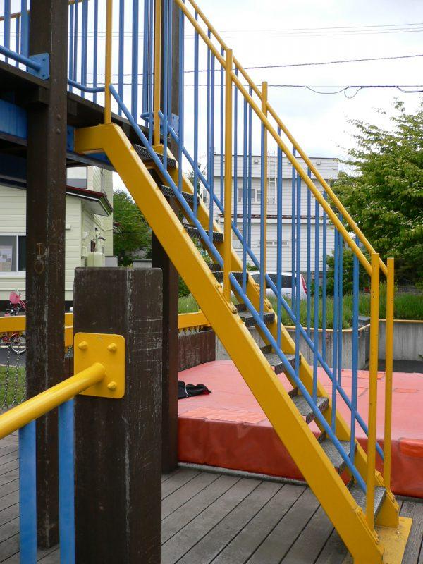 写真:2階デッキへ通じる階段。傾斜は約55度。両側に高めの手すりが付いている