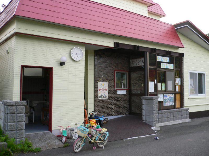 写真:むくどりホームの入口。子どもの三輪車などが置かれ、壁には「あいています」の手作りタペストリーが掛かる。手前は柴川さんが子どもたちのために作られた多目的トイレ