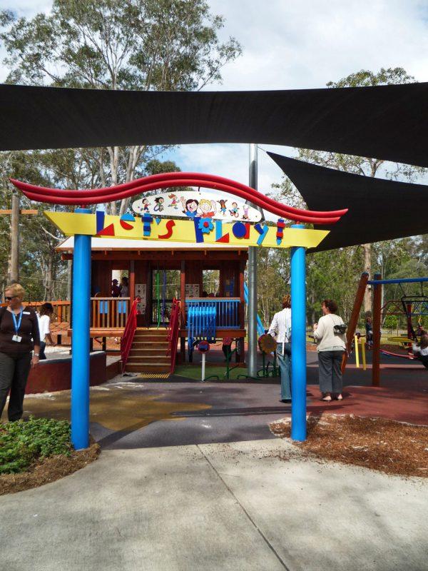 写真:パイオニアパークに作られた遊び場の入口。多様な子どもが遊んでいるイラストと共に「レッツ プレイ!」と書かれたゲートが立っている