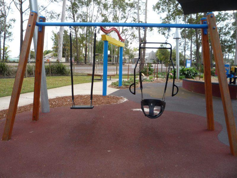写真:並んで吊られている2つのブランコ。左は板ブランコ。右は腰を覆う形にカーブした座面でシートベルトがついている。鎖の両脇にはそれと平行するように上から伸びた2本の握りバー