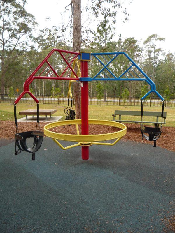 写真:円形の回転遊具。上から3つのシートが吊られている。地面は衝撃を吸収するゴムチップ舗装